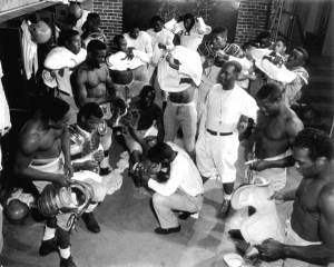 Coach_Jake_Gaither_(standing,_middle,_white_shirt)_in_the_locker_room_with_his_Florida_Agricultural_and_Mechanical_University_(FAMU)_football_team